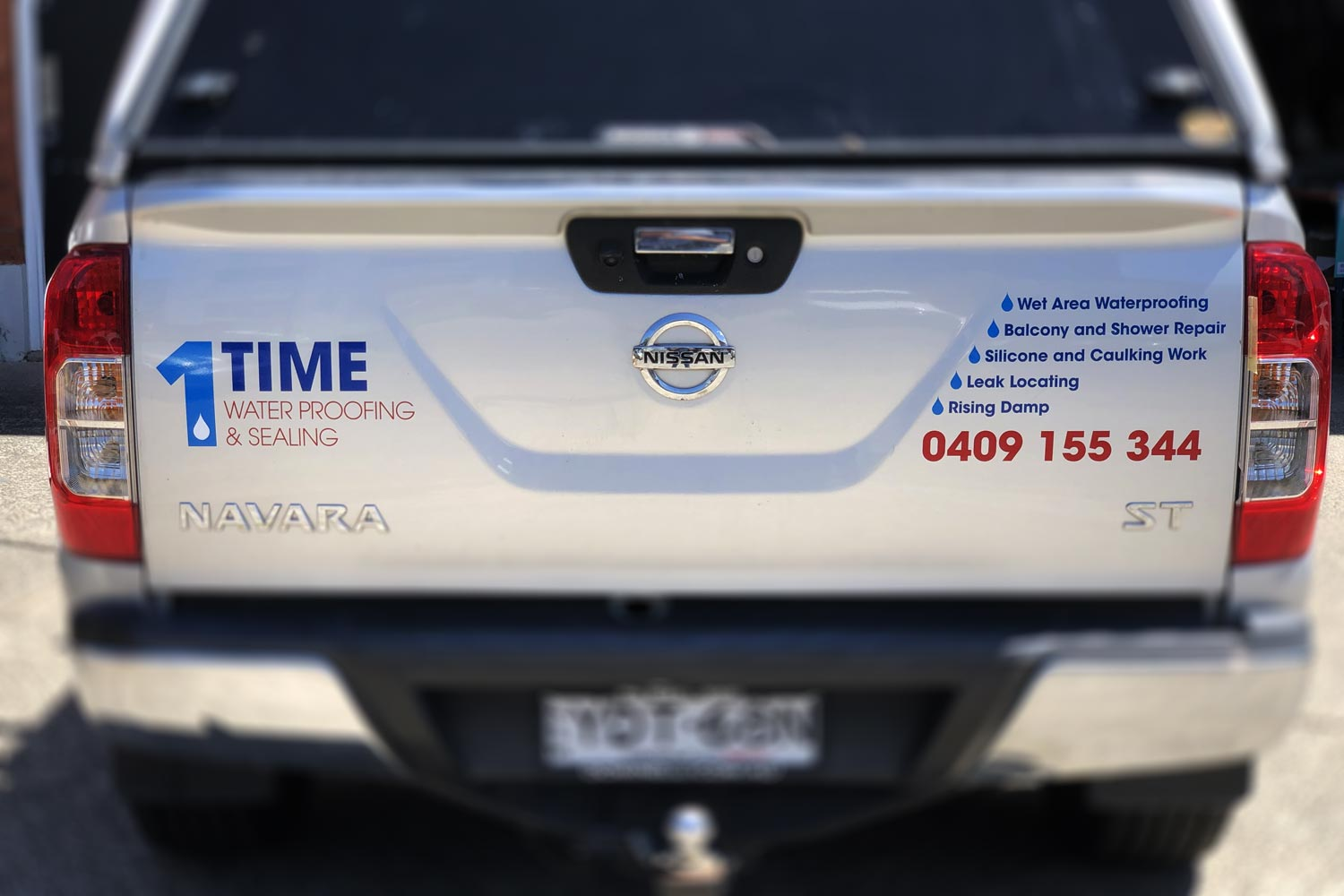 1Time Waterproofing Nissan back with signage